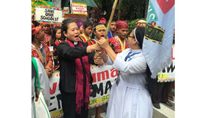 Oct. 12, 2018 Salubong of the Lumads and the Benedictine Community. Sr. Christine Pinto, OSB receives the Save Our Schools Flag.