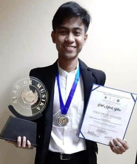 Grade 12 music student Edel Mark Bitao proudly holds up his certificate and trophy, representing his first-place standing on the highly regarded National Music Competitions for Young Artists.